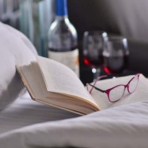 book and glasses sitting on hotel bed