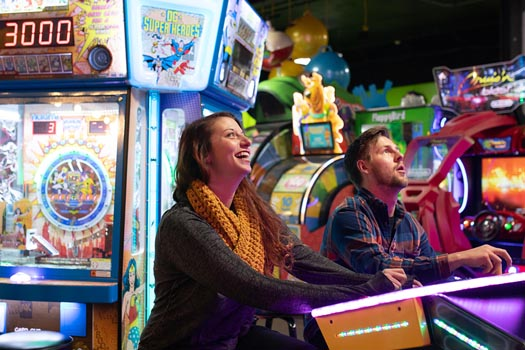 Man and woman playing arcade game