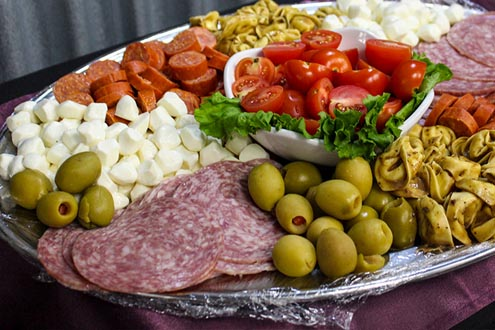 Antipasto platter with olives, cheese, salami, tomatoes, and more.