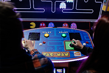 Two people playing pac-man game