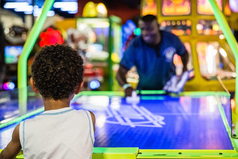 Father and son playing air hockey