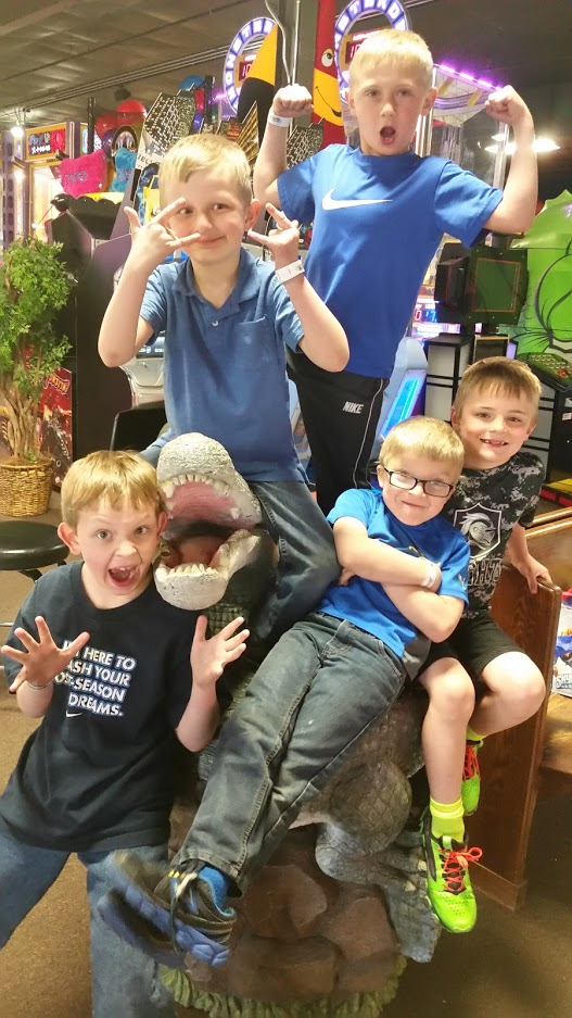 Group of boys making silly face next to a stuff alligator