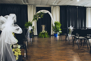 Wedding ceremony seating with arch covered in white tulle