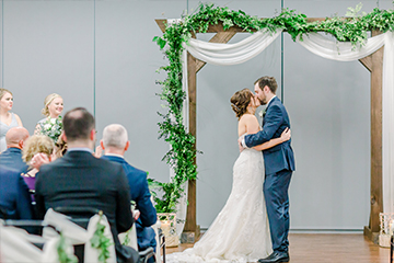 Couple kissing under arch at their wedding ceremony
