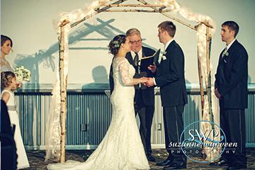 Couple reciting their vows underneath a wooden arch