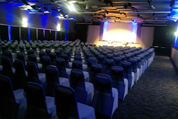 Theatre style wedding ceremony seating with blue uplighting