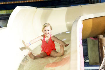 Little Girl going down water slide