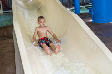 Little boy sliding down water slide