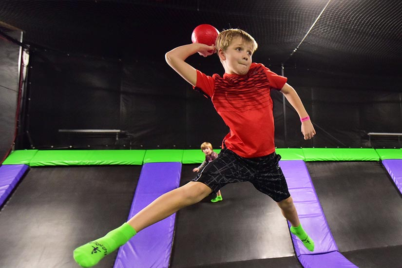 Boy in red shirt throwing dodgeball