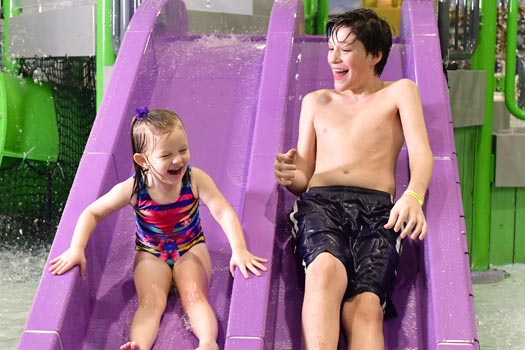Boy and girl sliding down double water slide