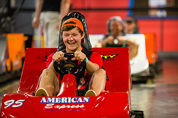 Boy in red shirt driving red go-kart