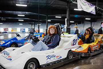 Woman with curly red hair in white go-kart