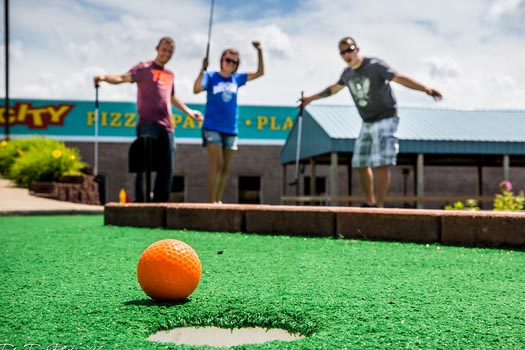 teenagers playing mini-golf