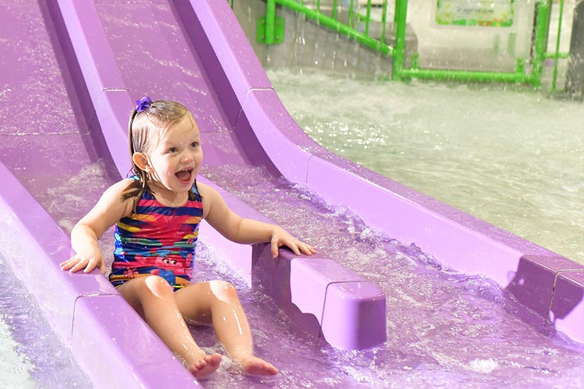 Little Girl going down double water slide