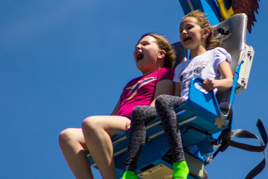 Two girls screaming on the zipline