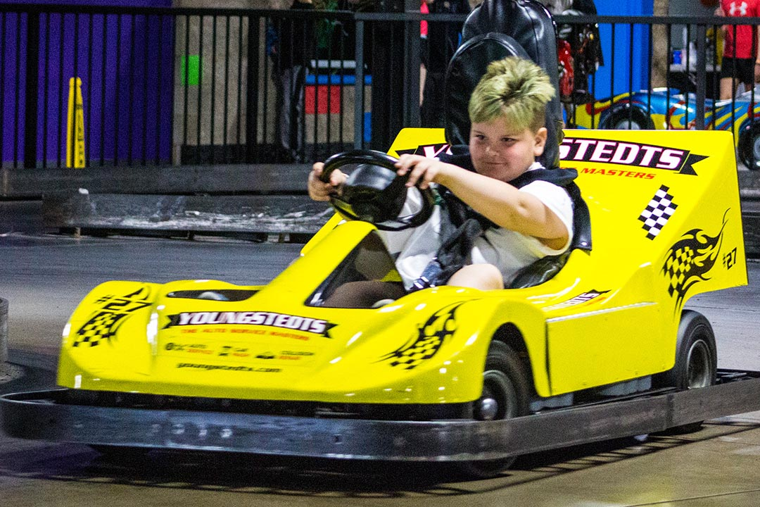 Boy driving yellow go kart.