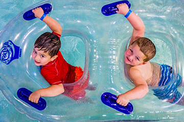 Boys in a double tube on the lazy river