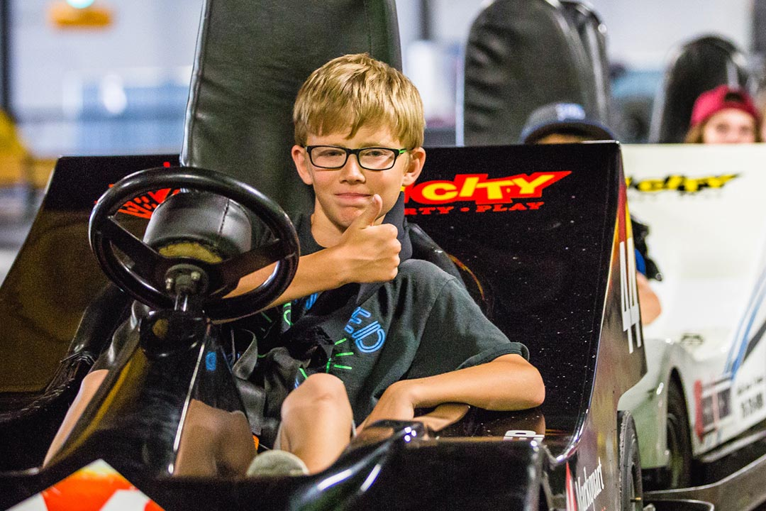 Kid giving thumbs up on go-kart