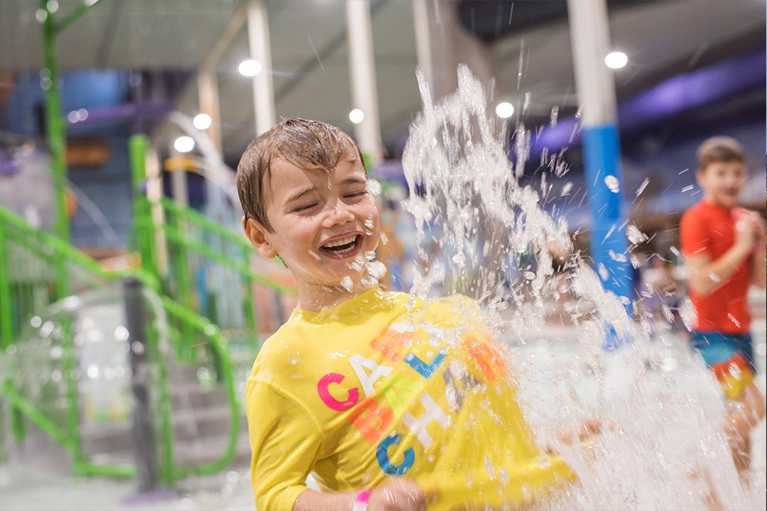 Boy in yellow shirt laughing while being splashed with water.