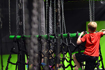 Boy climbing rope bridge on ninja warrior course