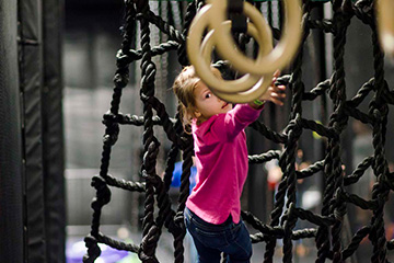 Little girl grabbing for rings on ninja warrior course