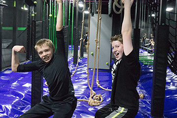 Two boys showing off on ninja warrior course