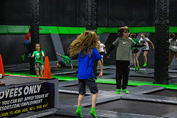 Kids jumping in open trampoline court