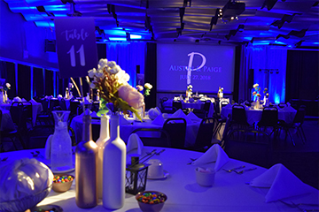Skybox banquet hall with reception style seating and blue uplighting