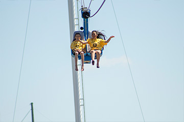 Two girls in yellow shirts high up on the zipline